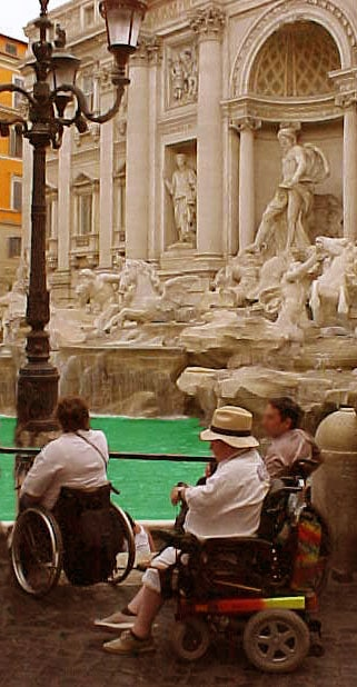 Italy easier for All! Tourists by wheelchair if front of Trevi Fountain, Rome, Italy